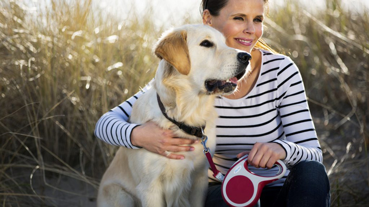 woman hugging her dog and holding a Flexi dog leash