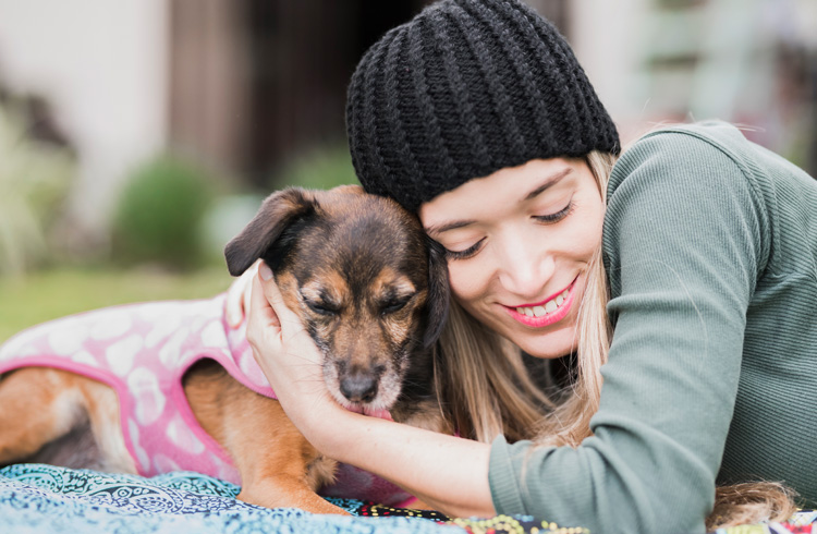 Image of pretty woman cuddling her dog