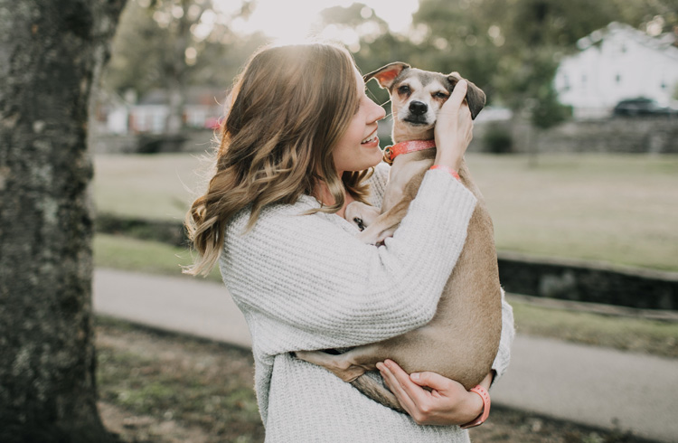 Image of pretty woman hugging small canine